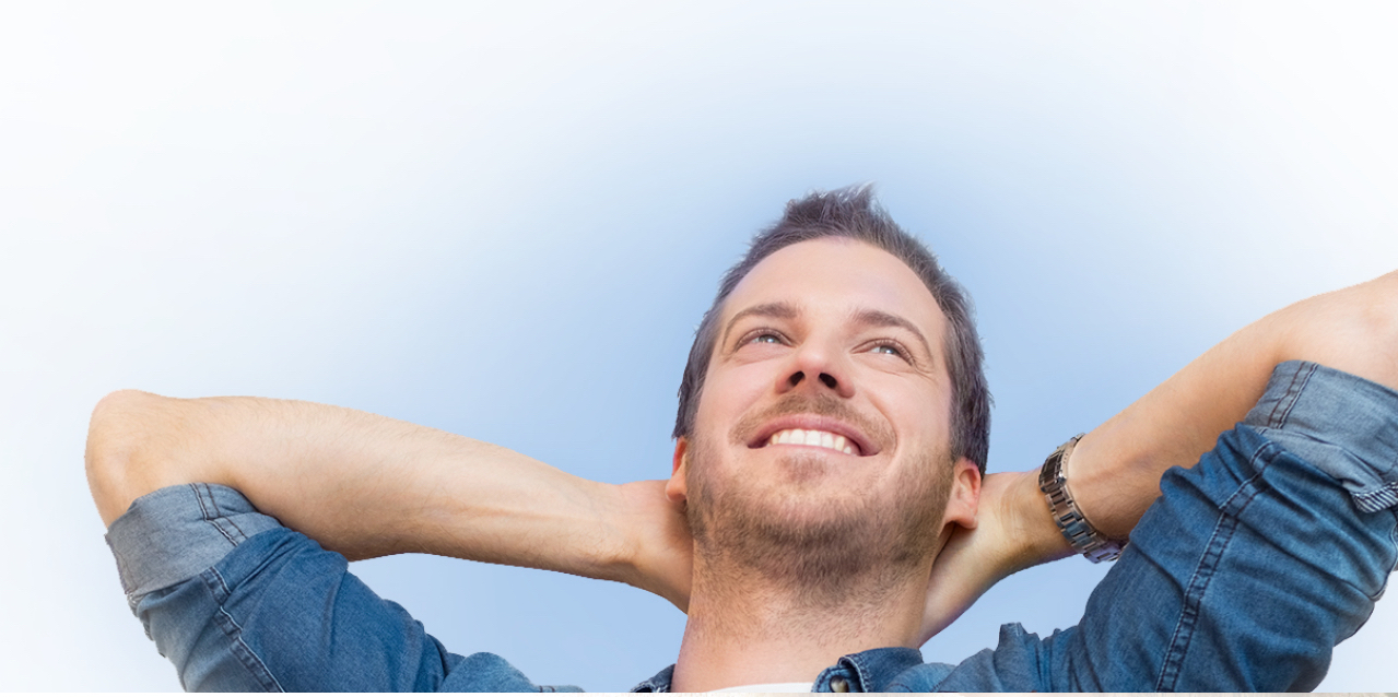 Bearded man with hands behind head looking to the sky smiling because of dental implants
