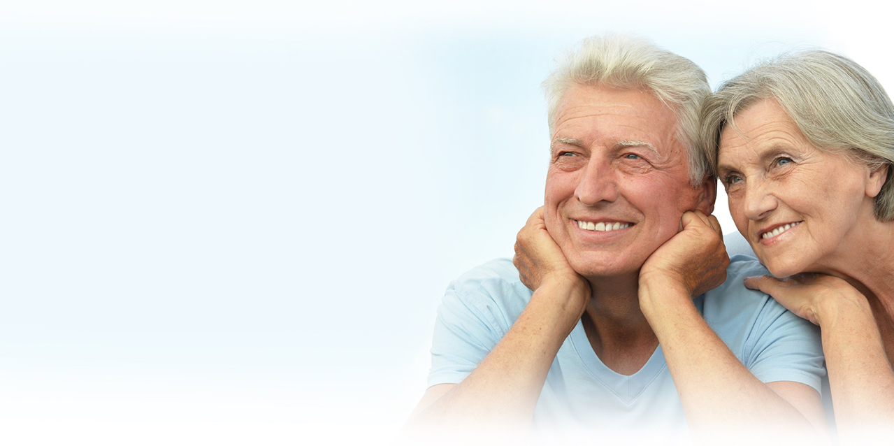 Smiling silver haired middle-aged couple with perfect dental implants