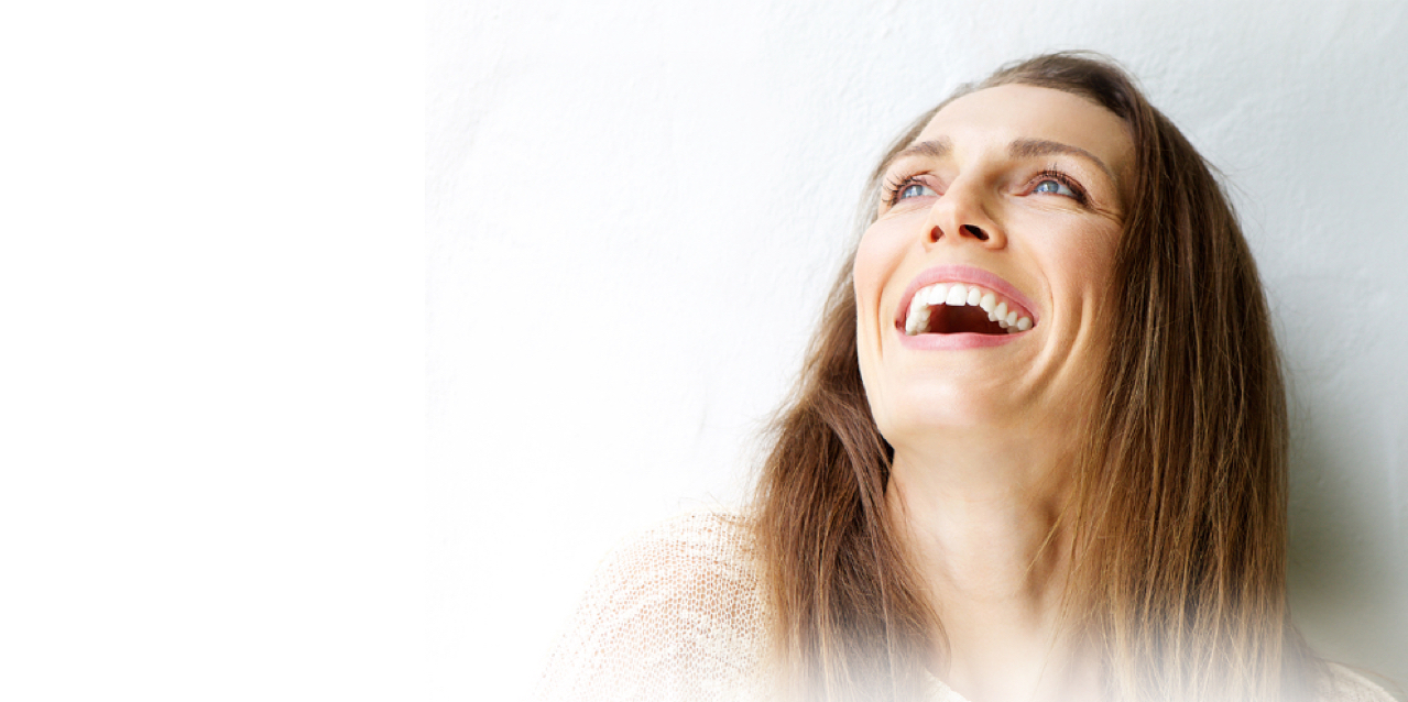 Brunette woman looking up and showing dental implants with open-mouth smile