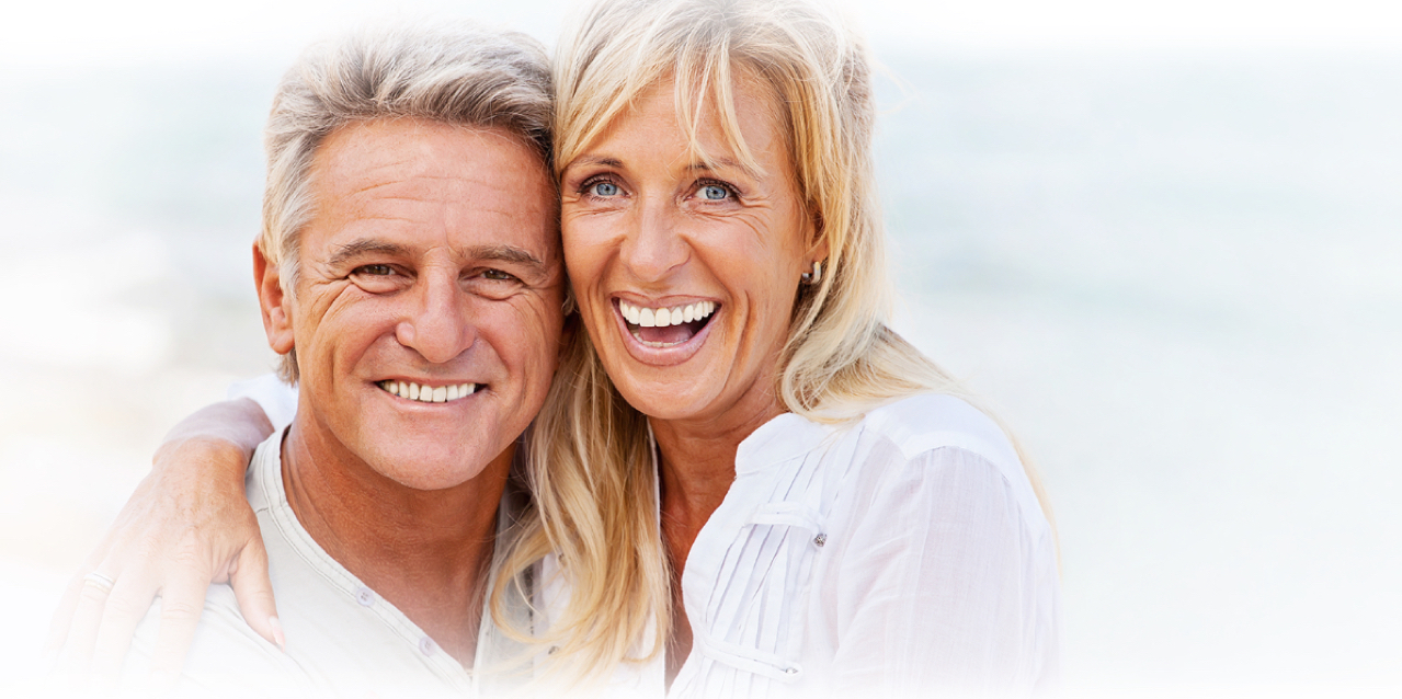 Smiling middle-aged woman with dental implants embracing silver-haired husband
