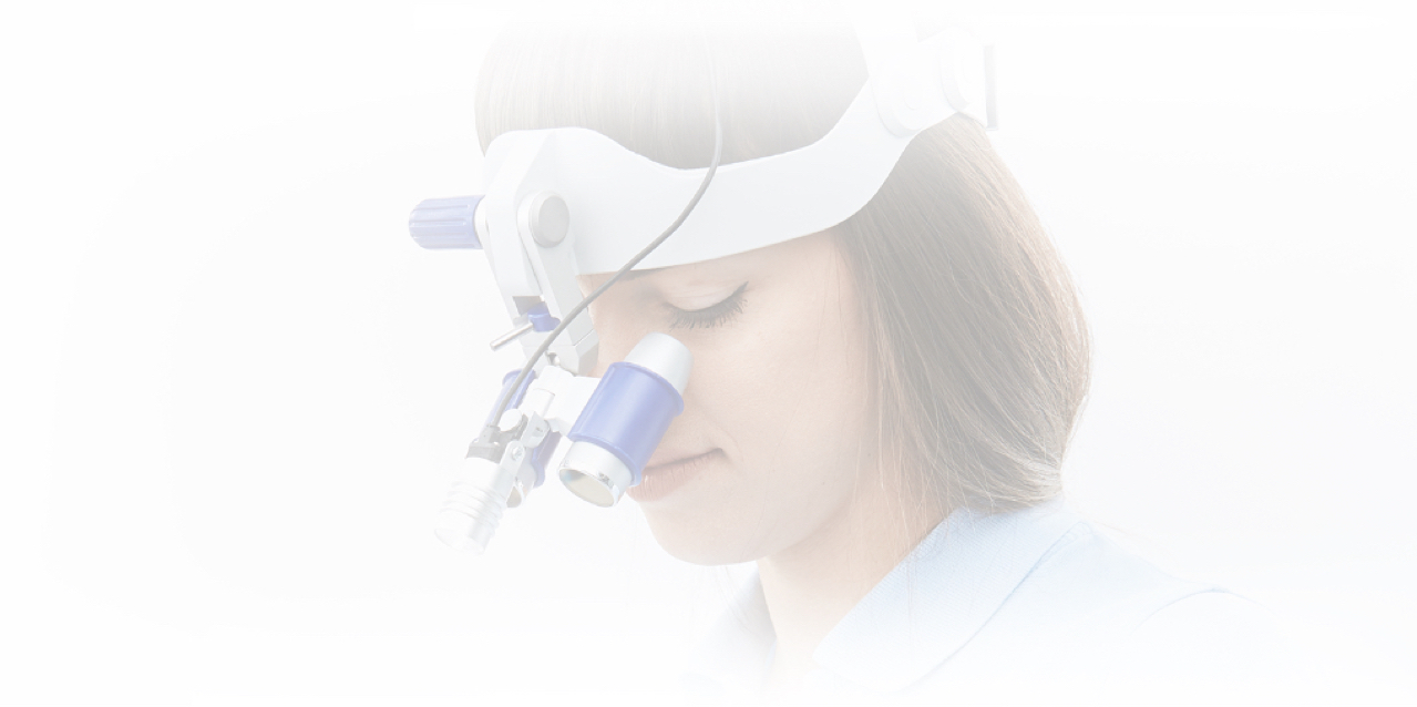 Female dentist looking through Loupes during dental implant examination