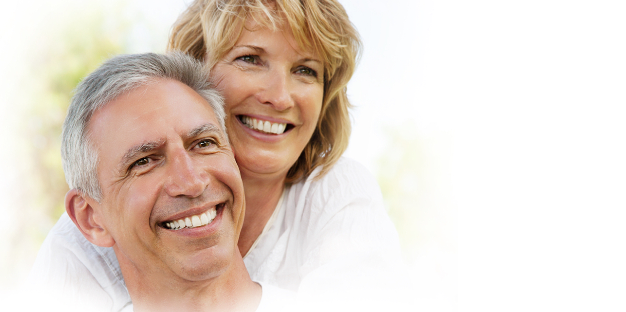 Smiling woman hugging man with implant supported dentures