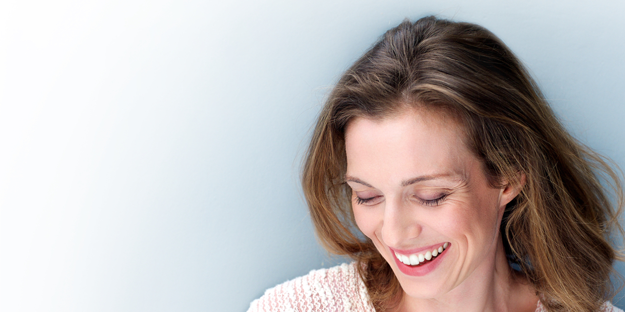 Woman looking down and smiling with dental implants